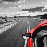 Red car driving on a road under an open sky
